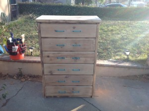 Here is what it looks like with the drawers in and handles on after being sanded.